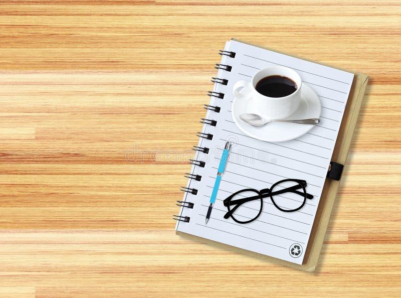有办公用品的笔记本与与玻璃和杯子的笔c 免版税图库摄影