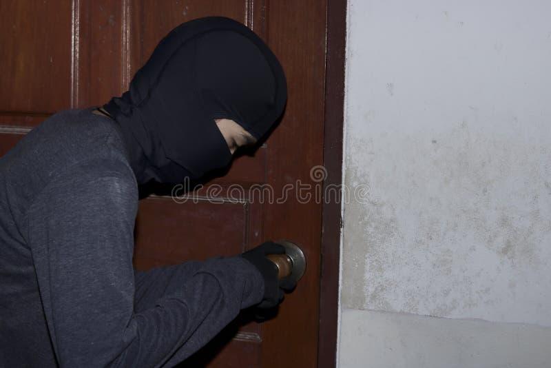 有加入和闯入房子的巴拉克拉法帽的被掩没的夜贼在夜间 砖概念罪行前面现有量苛刻的藏品手枪影子墙壁 库存照片