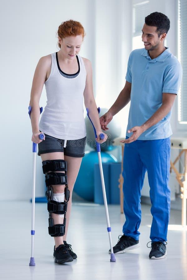 有加强筋的生理治疗师帮助的妇女在腿 免版税图库摄影
