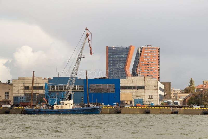 有动臂起重机的在克莱佩达海港附近,岩性学老装载的船 免版税图库摄影