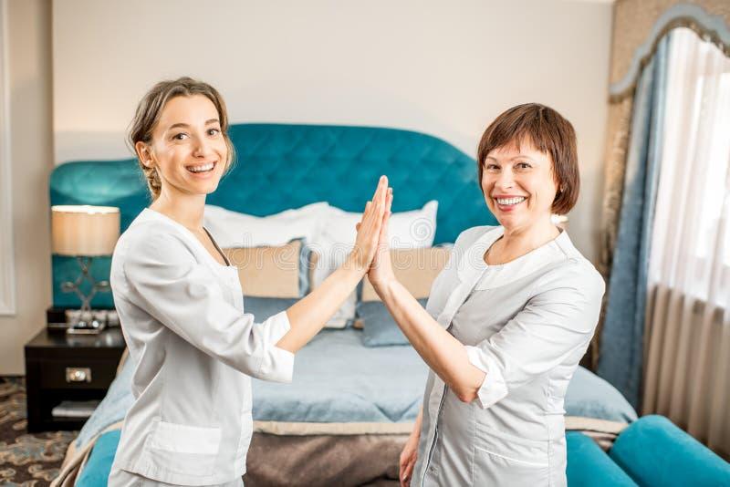 有助理的资深女服务生在旅馆客房 免版税库存图片
