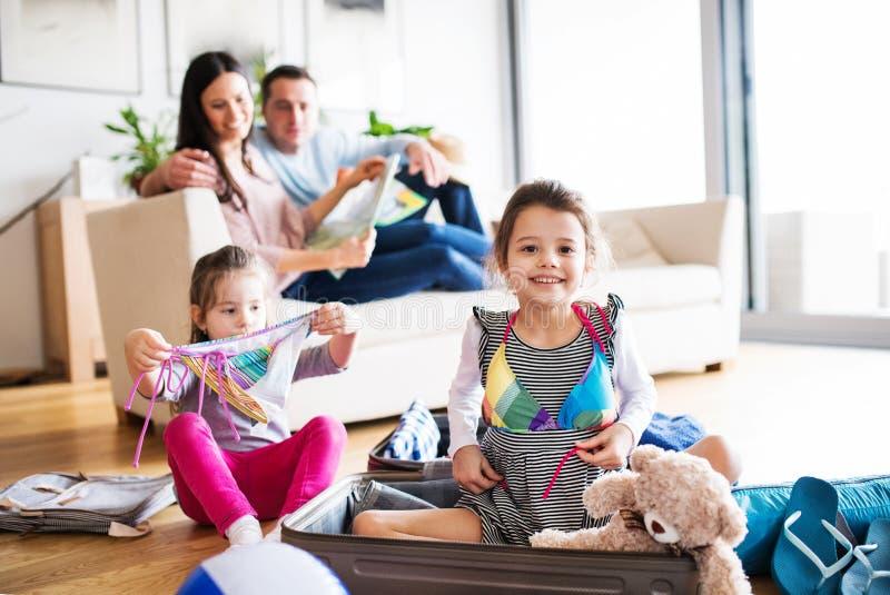 有包装在假日的两个孩子的年轻家庭 库存图片