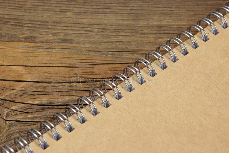 有包装纸盖子的闭合的笔记本在木土气表上 图库摄影