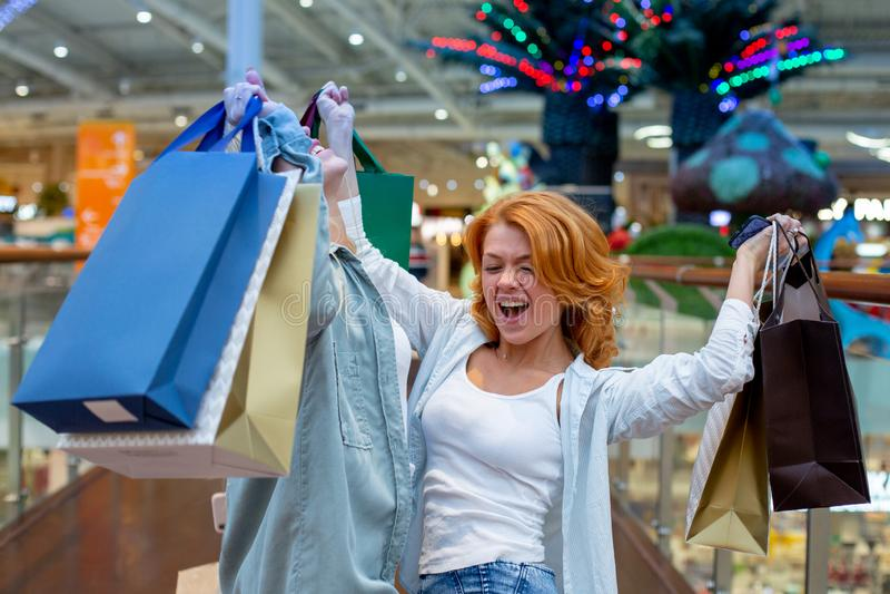 有包裹的少妇购物在现代购物中心的 背景袋子概念行程购物的白人妇女 黑星期五概念 愉快的妇女 拿着包裹 免版税库存照片