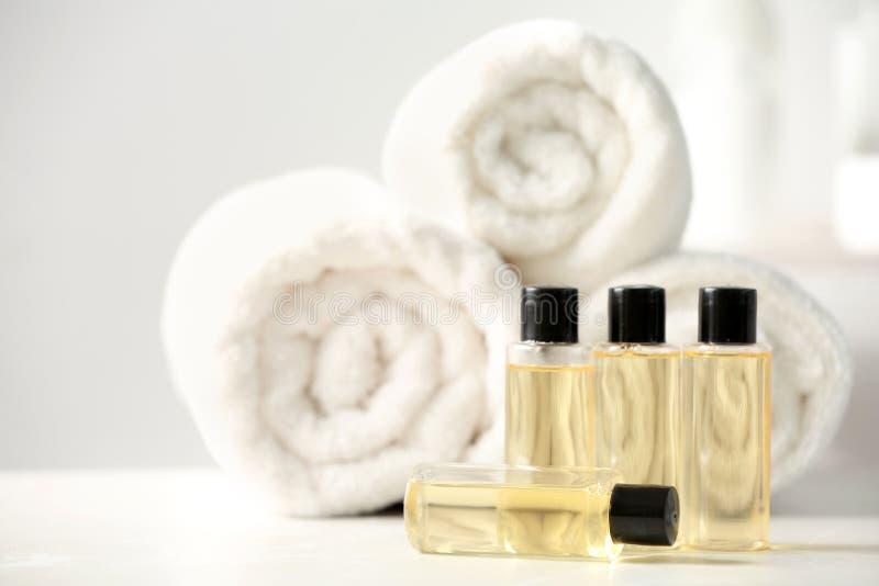 有化妆品和毛巾的微型瓶在桌,文本的空间上 库存照片