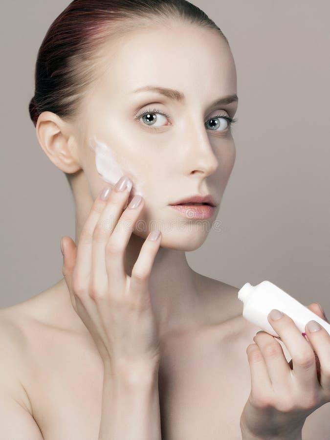 有化妆奶油的美丽的女孩在面孔 图库摄影