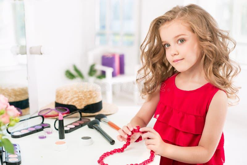 有化妆用品的一个小女孩 她在母亲` s卧室,坐在镜子附近 库存照片