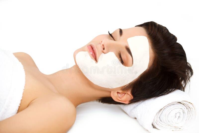 有化妆面具的美丽的妇女在面孔。女孩得到治疗 库存照片