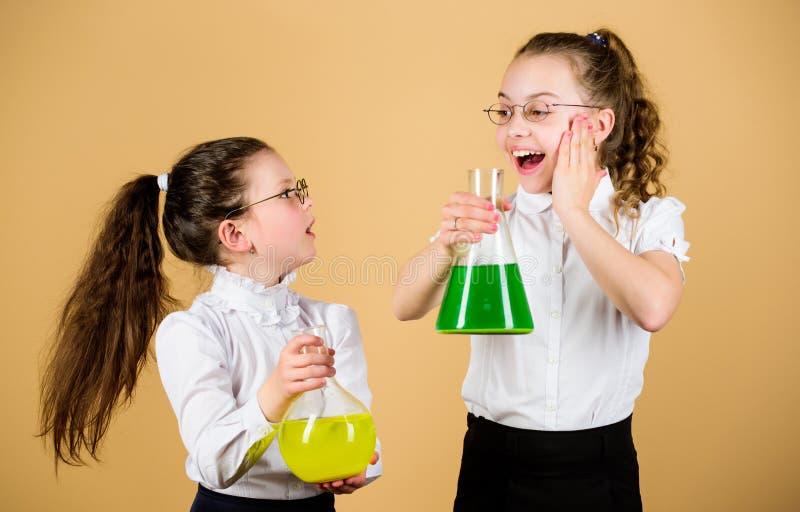 有化工液体的女小学生朋友 童年和养育 知识和信息 一起试验 免版税库存照片