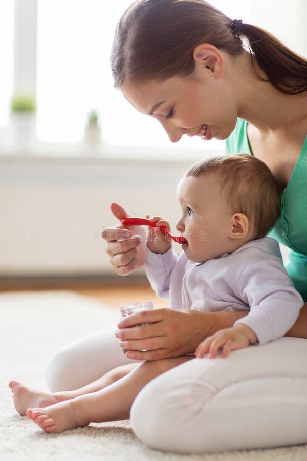 有匙子哺养的婴孩的愉快的母亲在家 免版税库存照片