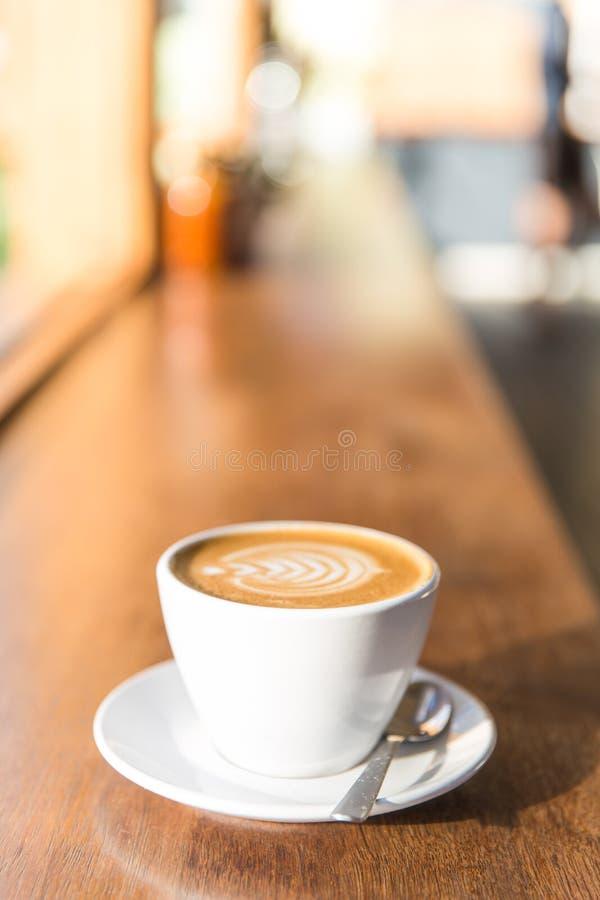 有匙子的咖啡杯在咖啡馆长凳 库存照片