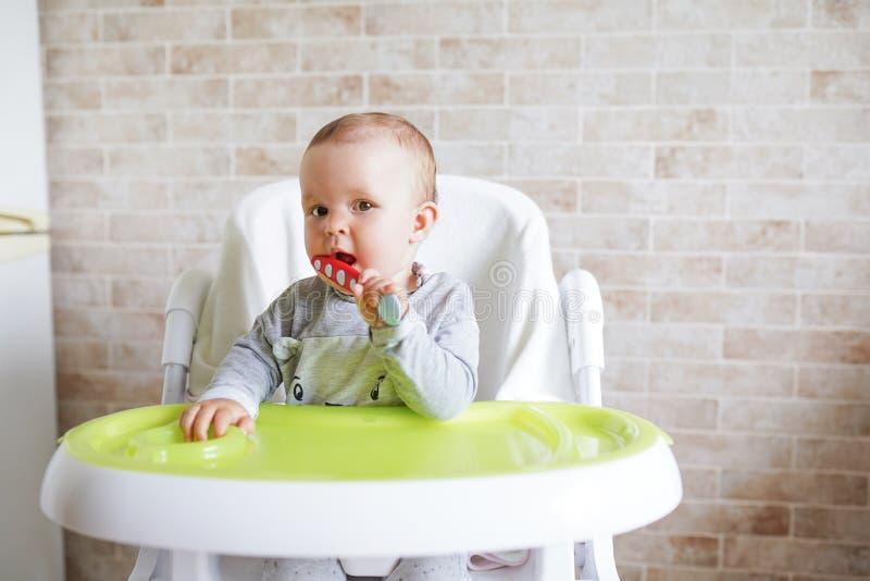 有匙子的婴孩在餐厅,微笑和愉快的孩子的椅子 r E 库存照片
