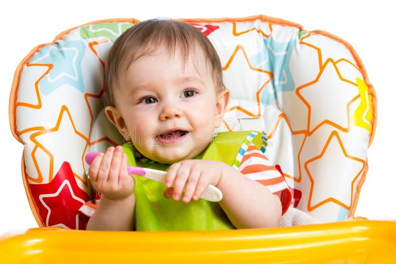 有匙子的微笑的男婴 库存照片