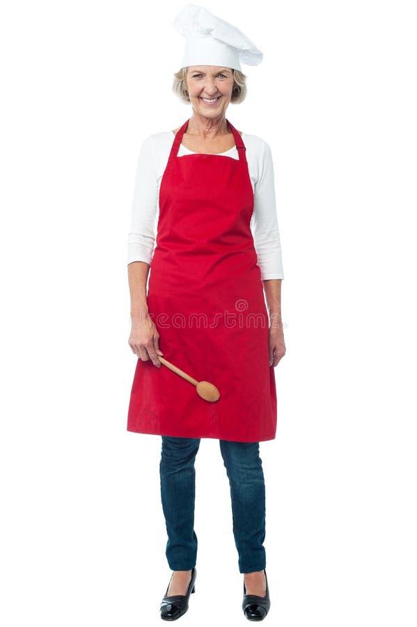 有匙子的快乐的资深女性厨师 免版税库存照片