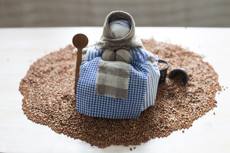 有匙子的玩偶在荞麦堆 免版税库存图片