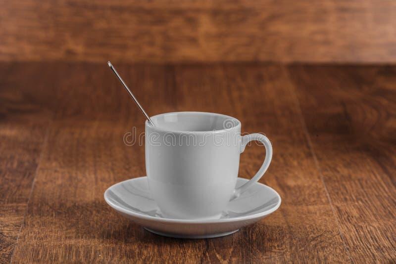 有匙子的白色coffe杯在黑褐色木背景的白色茶碟 库存图片