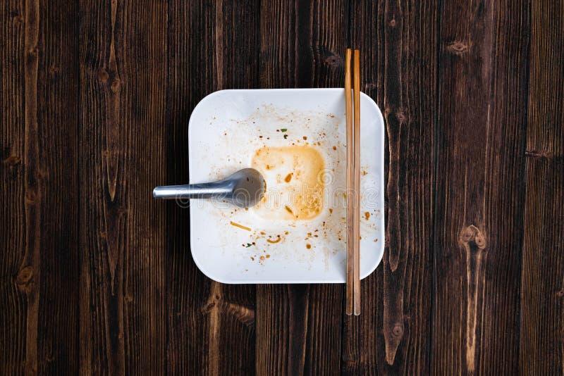 有匙子的空的白色面条碗和筷子以后在w吃 免版税库存照片