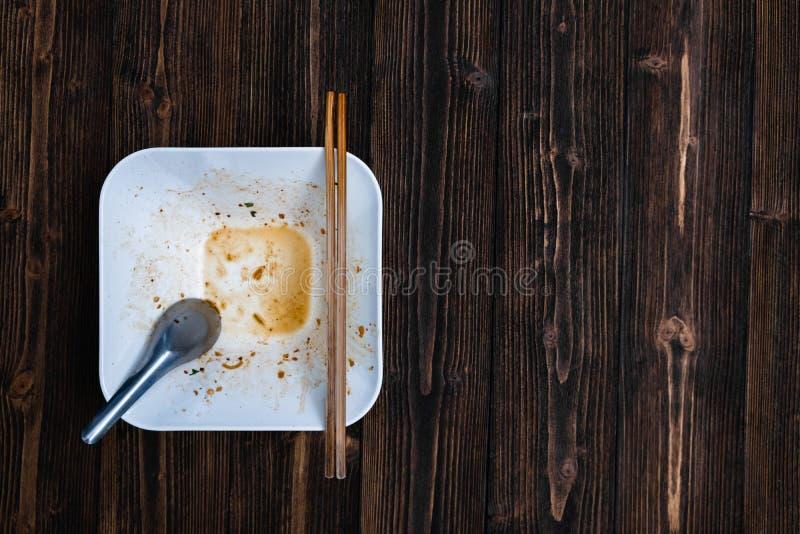 有匙子的空的白色面条碗和筷子以后在w吃 库存照片