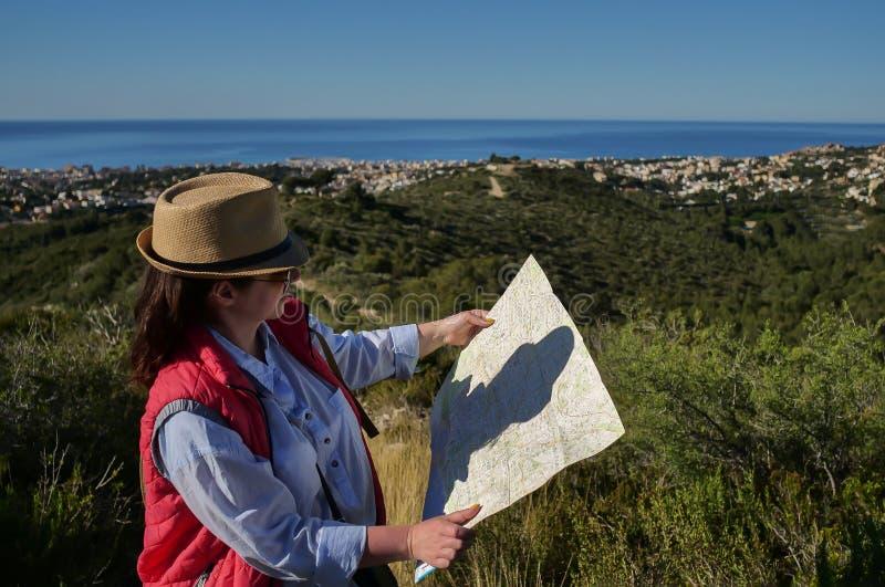 有区域看看的帽子和地图的年轻可爱的妇女游人在小山下的城市 库存照片