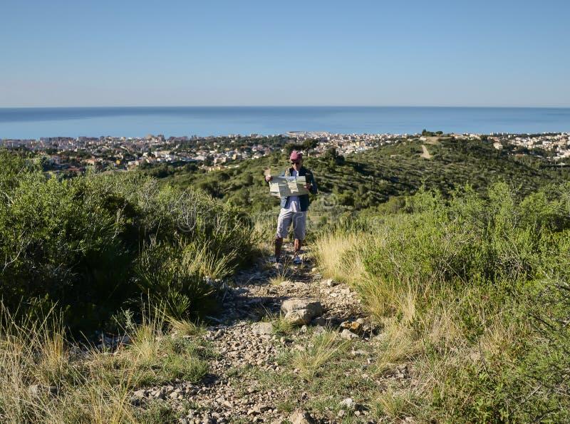 有区域立场的地图的年轻男性游人在一条石道路的在小山 免版税图库摄影