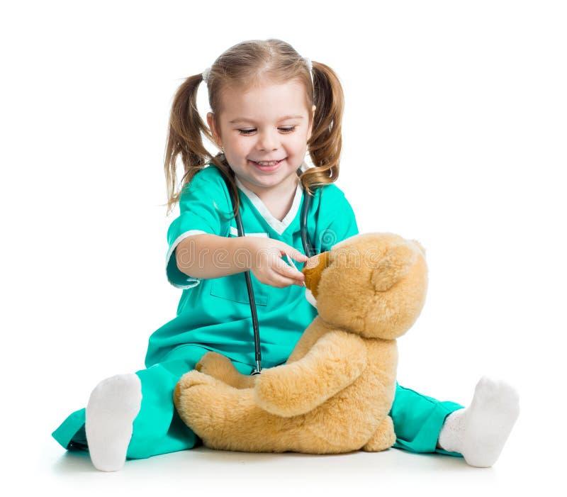 有医生和玩具熊衣裳的可爱的子项  免版税库存图片