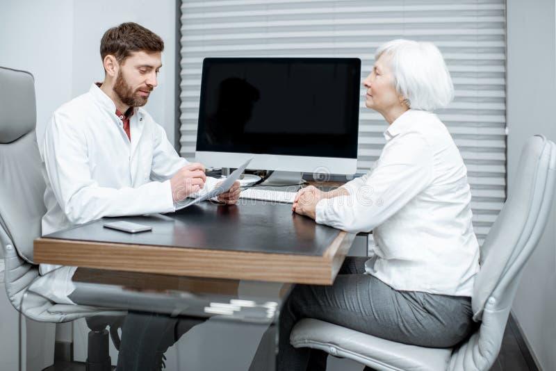 有医生的资深妇女在办公室 免版税图库摄影