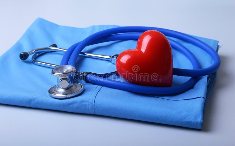 有医疗听诊器的医生在书桌上的外套和红心 库存照片