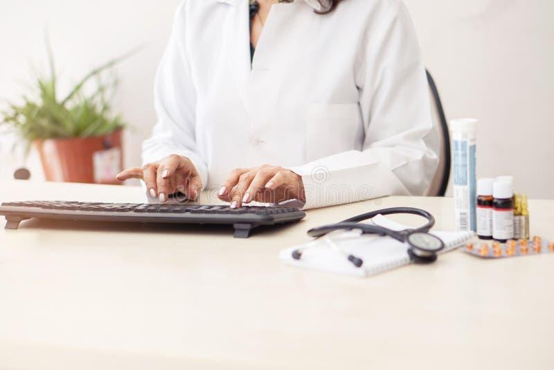 有医疗听诊器的和医学的白色实验室外套、手键入在手提电脑键盘的女性医生在镜子书桌上 库存图片