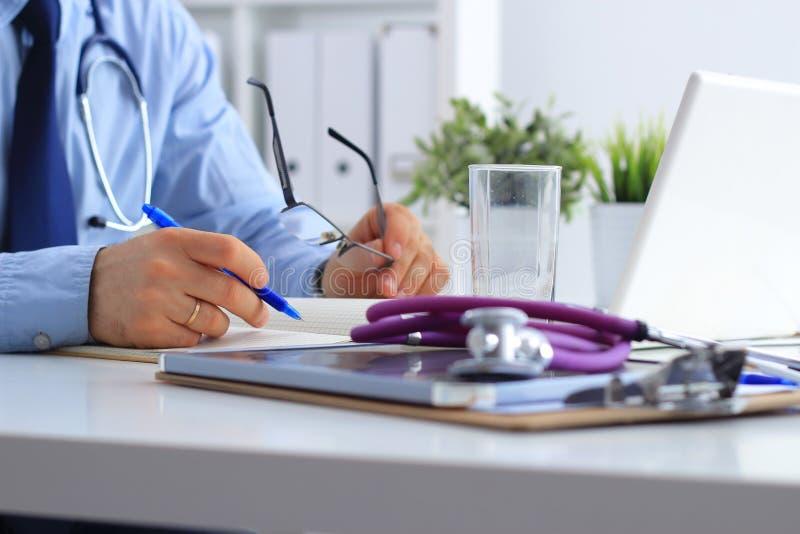 有医疗听诊器的男性医生使用膝上型计算机,坐在他的书桌 免版税图库摄影