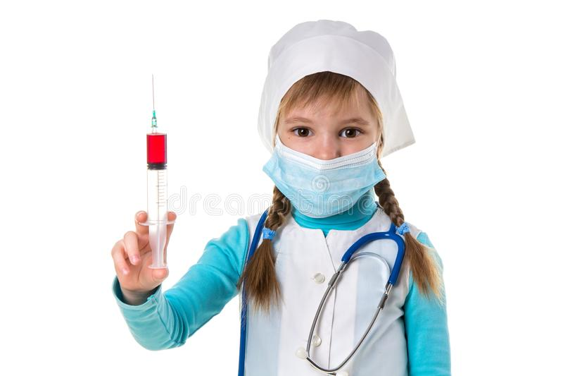 有医疗面膜的护士,垂直拿着有红色液体的注射器,看照相机,在白色风景 免版税库存图片