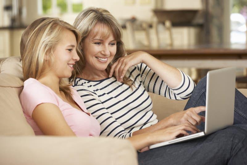 有十几岁的女儿的母亲在家坐沙发使用膝上型计算机 免版税库存图片
