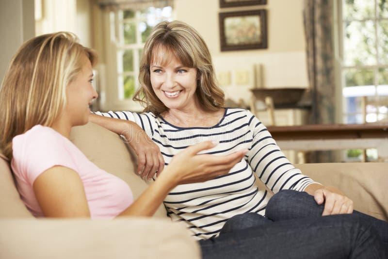 有十几岁的女儿的聊天的母亲在家坐沙发 库存照片