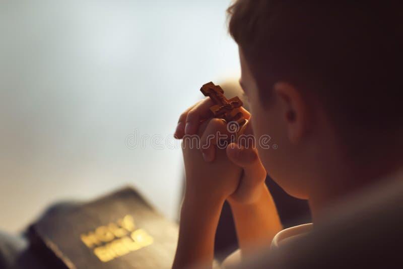 有十字架的在家祈祷的小男孩 库存图片