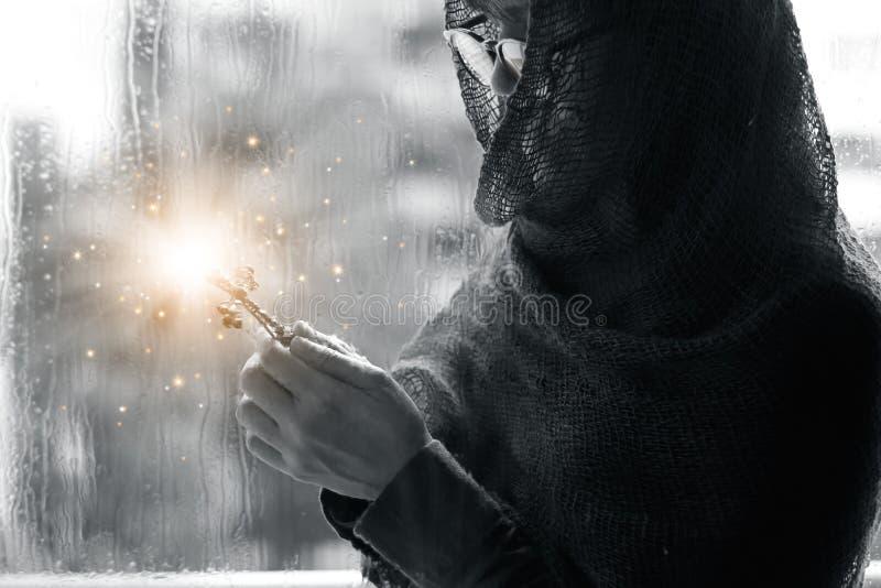 有十字架的基督徒妇女在手上祈祷希望和崇拜在雨珠背景的 抽象照明设备 圣餐疗法bles 图库摄影