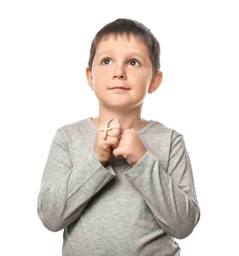 有十字架的小男孩祈祷在白色背景的 免版税库存照片