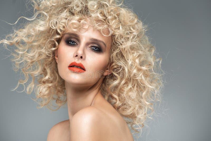 有华美的卷曲发型的美丽的白肤金发的夫人 免版税图库摄影