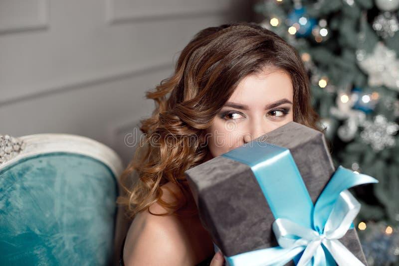 有华美的波浪发的,明亮的构成一少女,在她的手上在一把黄美英色椅子拿着一件被包裹的礼物,坐 库存照片