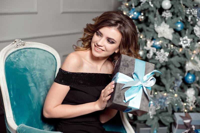 有华美的波浪发的,明亮的构成一少女,在她的手上在一把黄美英色椅子拿着一件被包裹的礼物,坐 免版税库存图片
