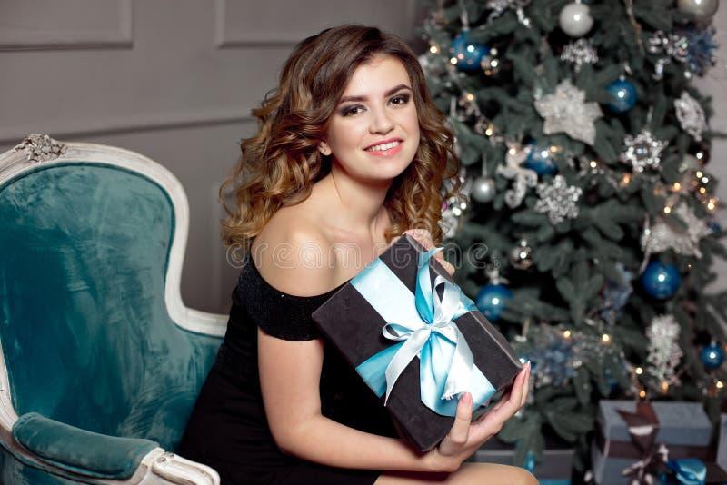 有华美的波浪发的,明亮的构成一少女,在她的手上在一把黄美英色椅子拿着一件被包裹的礼物,坐 免版税库存照片