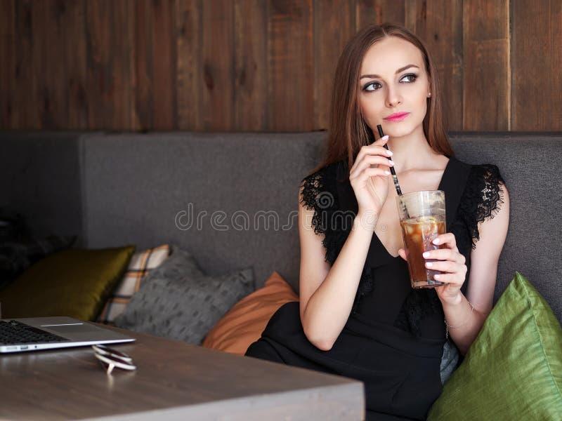 有华美的眼睛时髦构成和时髦的成套装备的年轻可爱的妇女喝大玻璃咖啡与秸杆的使用noteboo 库存照片