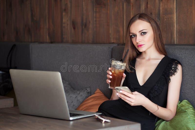 有华美的眼睛时髦构成和时髦的成套装备的年轻可爱的妇女喝大玻璃咖啡与秸杆的使用noteboo 图库摄影