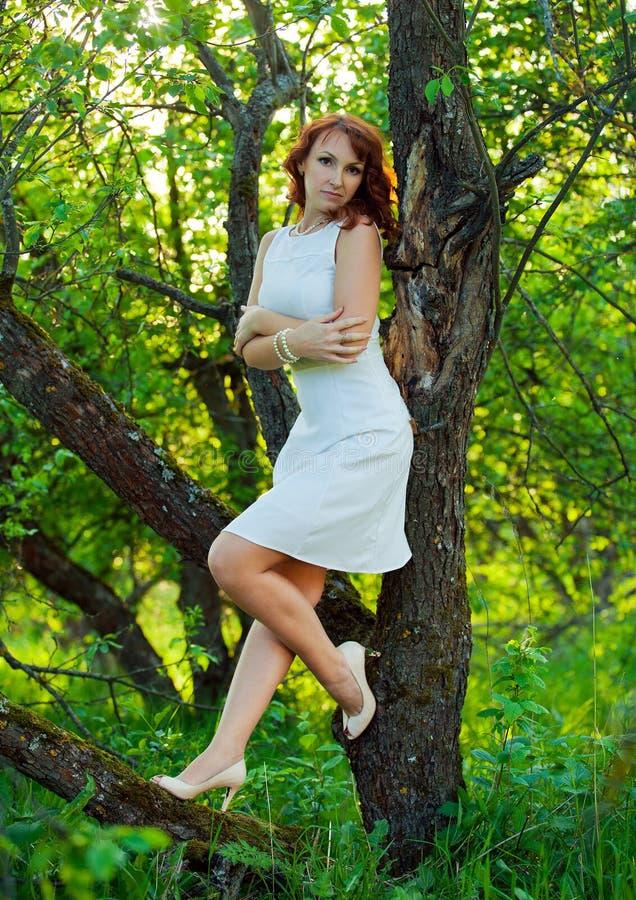有华美的红色头发的自由的愉快的妇女享受自然的 秀丽女孩室外在春天庭院里 查出的黑色概念自由 免版税库存图片