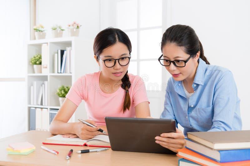 有单独家庭教师的俏丽的大学生女孩 免版税库存图片