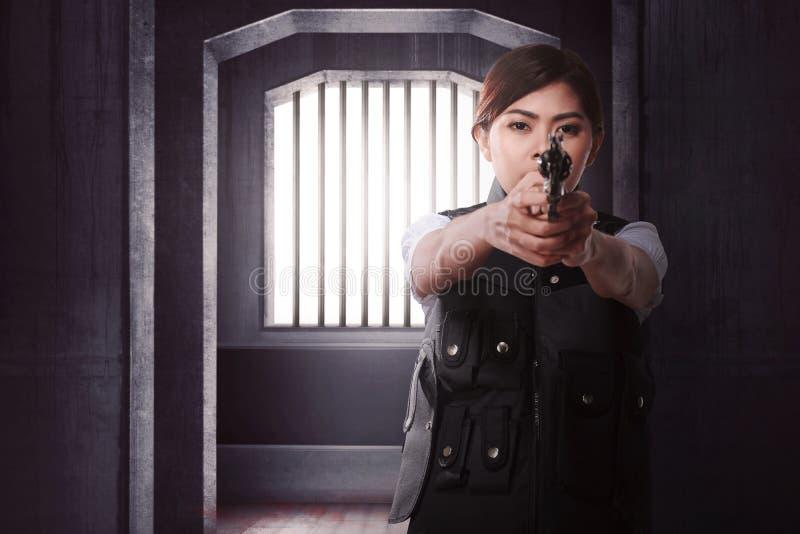有单独站立的枪的美丽的亚裔妇女 免版税库存照片