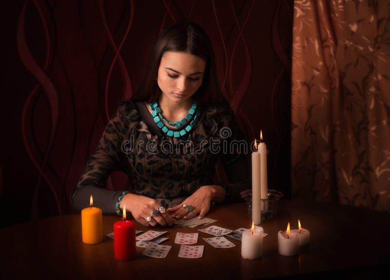 有占卜卡片的妇女在屋子里 免版税库存照片