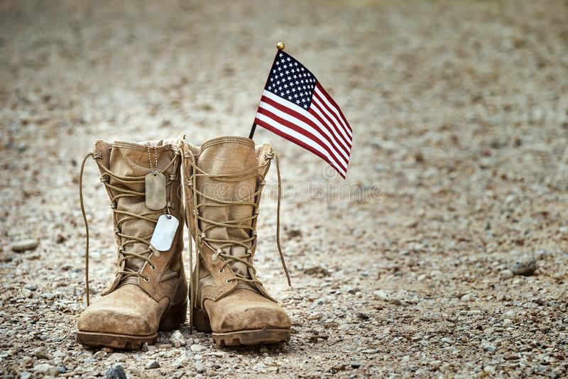 有卡箍标记和一面小美国国旗的老军用长统靴 库存图片