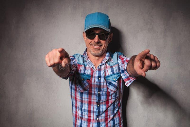 有卡车司机帽子的凉快的成熟偶然人指向他的手指的 免版税库存图片