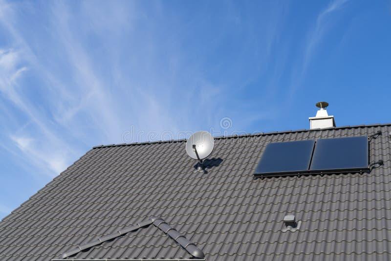 有卫星盘和小光致电压的系统的一个房子屋顶 库存图片