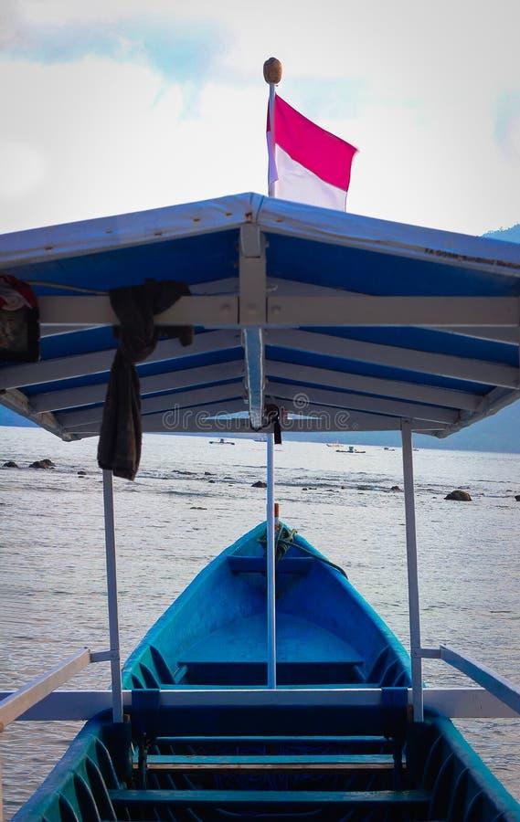 有印度尼西亚旗子航行的一条蓝色木小船在海滩 图库摄影