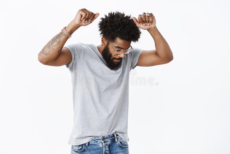 有卷发、看下来作为跳舞的胡子纹身花刺和被刺穿的鼻子的英俊和凉快的非裔美国人的成人人 库存照片